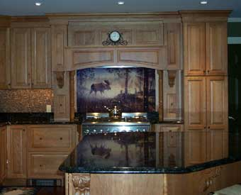 This moose  walking through the misty woods scene is perfect for a kitchen backsplash. This is an image of Jim Hansel's A Walk In The Mist artwork made on tumbled marble tiles and used as a tile mural behind the range.  The tile mural completes this gorgeous kitchen remodel